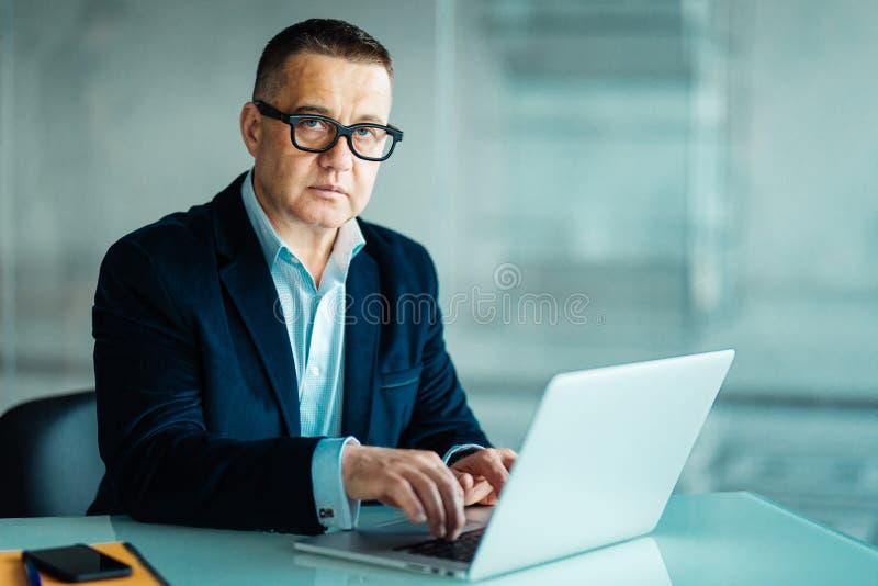 Portrait d'homme d'affaires supérieur bel utilisant un ordinateur portable tout en regardant l'appareil-photo photo libre de droits