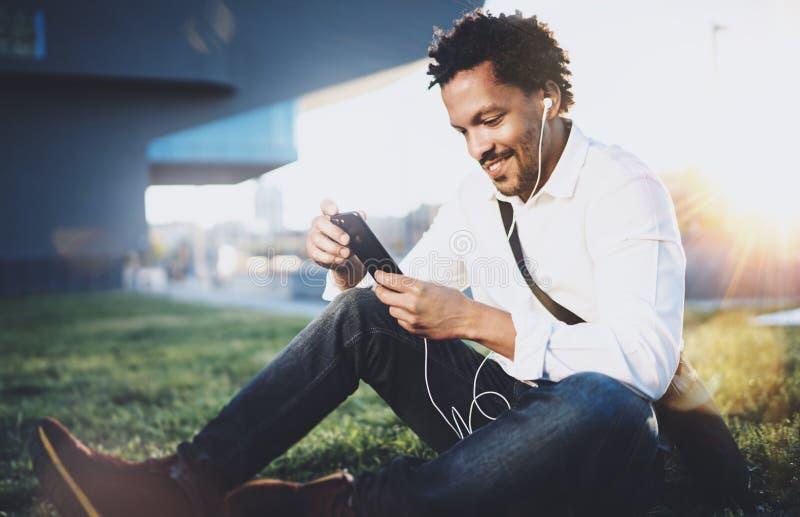 Portrait d'homme africain américain de sourire dans l'écouteur prenant le frein au parc ensoleillé et appréciant pour écouter la  photographie stock libre de droits