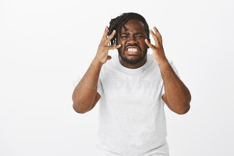 Portrait d'homme africain dodu contrarié fâché dans le T-shirt blanc, étant fâché ou sous pression, grimcaing avec serré images libres de droits