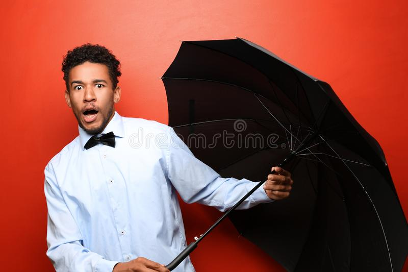 Portrait d'homme afro-américain effrayé avec le parapluie sur le fond de couleur photo stock