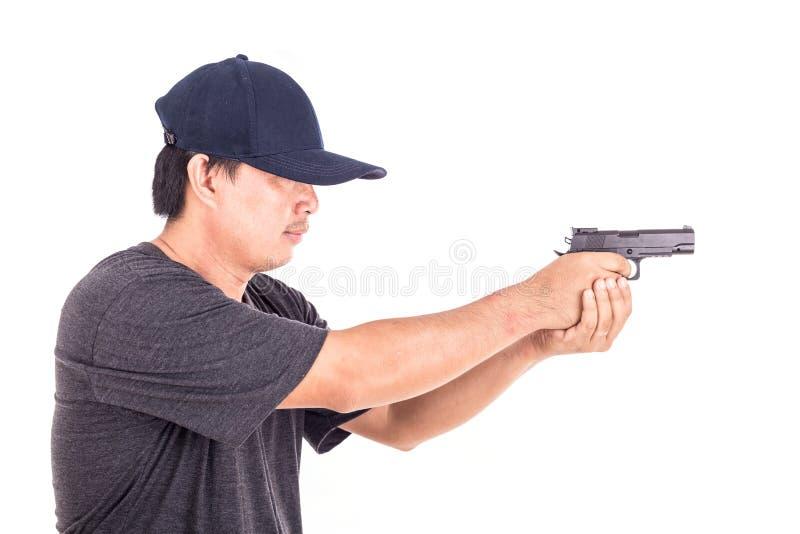 Portrait d'homme asiatique jugeant l'arme à feu d'isolement sur le blanc photo stock