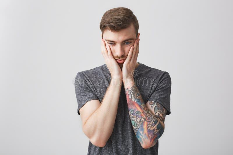 Portrait d'homme barbu caucasien bel avec la coiffure élégante et de tatouage sur le bras gauche étant fatigué et contrarié ensui photographie stock