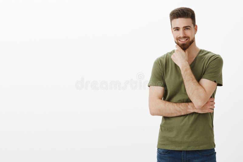 Portrait d'homme barbu caucasien de charismasitc avec du charme avec des yeux bleus frottant le menton en tant que sourire ravi à images libres de droits