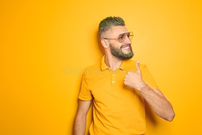 Portrait d'homme bel avec le geste teint de cheveux et de pouce- d'apparence de barbe sur le fond de couleur images libres de droits