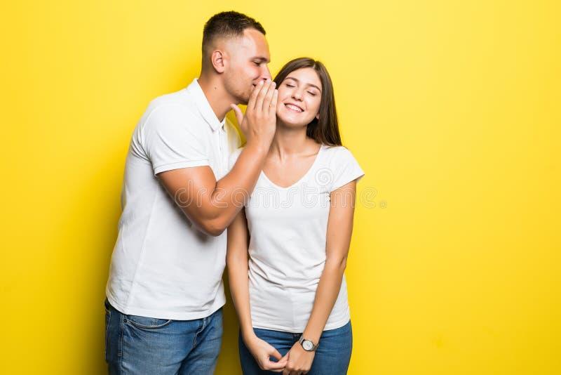 Portrait d'homme bel chuchotant le bavardage secret ou int?ressant ? la jeune femme dans son oreille d'isolement au-dessus du fon photos stock