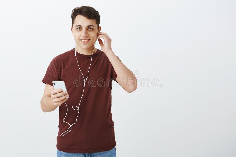 Portrait d'homme caucasien bel sortant avec les cheveux foncés courts, mettant sur des écouteurs et tenant le smartphone, obtenan photo stock
