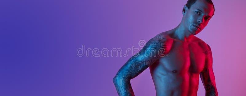 Portrait d'homme convenable de sport avec les bras tatoués Torse nu musculaire sur un fond bleu rose photographie stock