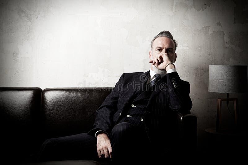 Portrait d'homme d'affaires adulte portant le costume à la mode et reposant le studio moderne sur le sofa en cuir contre le béton image libre de droits