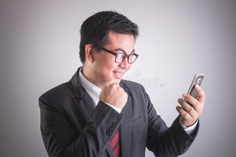 Portrait d'homme d'affaires asiatique tenant le smartphone Heureux ou excit photos stock