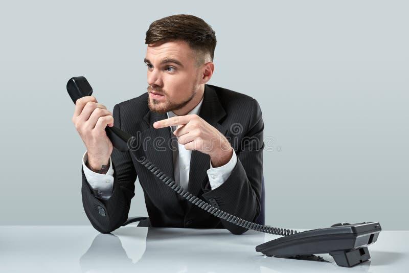 Portrait d'homme d'affaires attirant tenant le téléphone dans sa main Cet appel est pour vous concept image stock