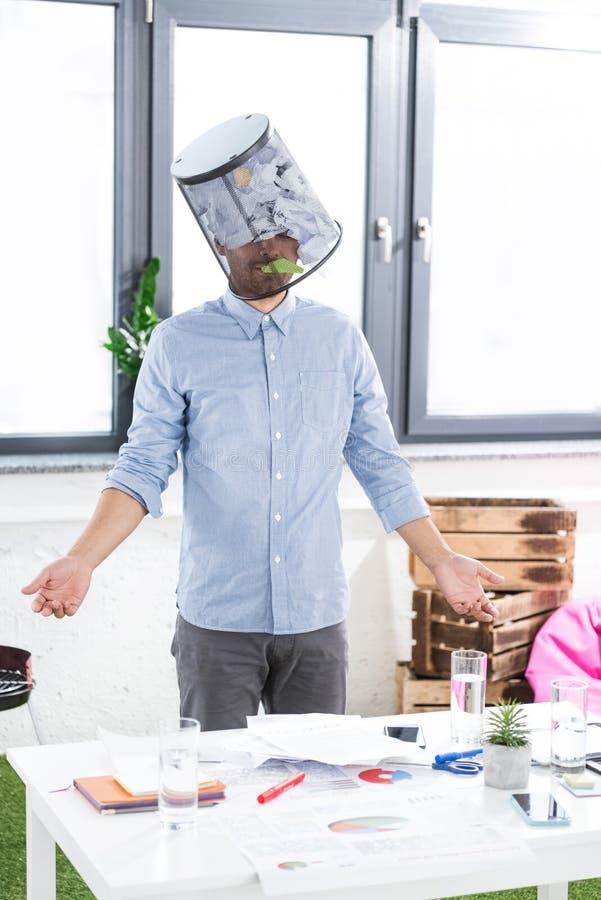 Portrait d'homme d'affaires confus avec le seau de déchets sur la tête dans le bureau photographie stock