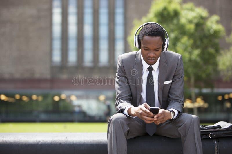 Portrait d'homme d'affaires d'Afro-américain écoutant la musique avec des écouteurs dehors photos libres de droits