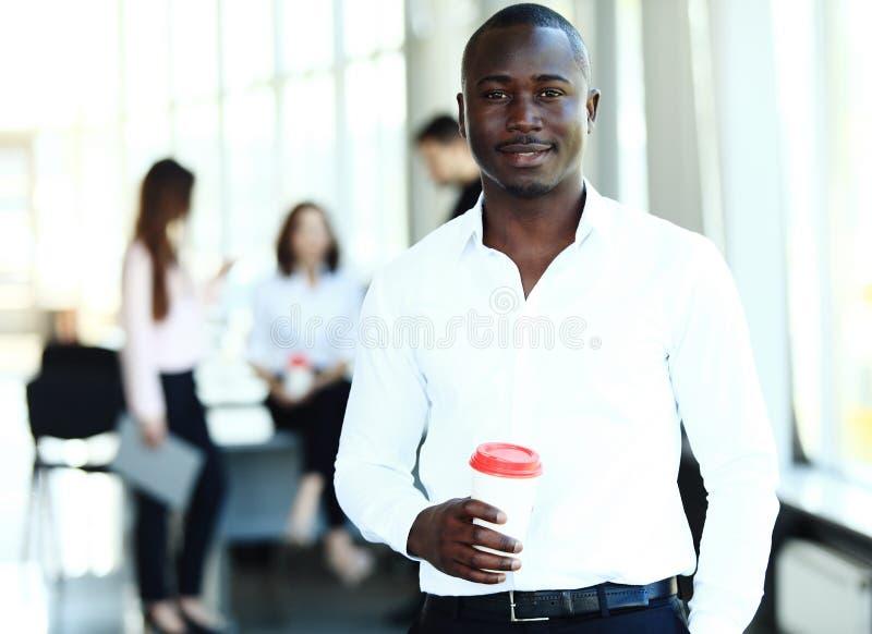 Portrait d'homme d'affaires d'Afro-américain avec des cadres fonctionnant à l'arrière-plan photo libre de droits