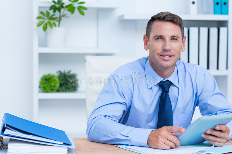 Portrait d'homme d'affaires de sourire utilisant son comprimé numérique image stock