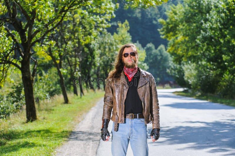 Portrait d'homme de cycliste avec la barbe se tenant sur la route photographie stock libre de droits