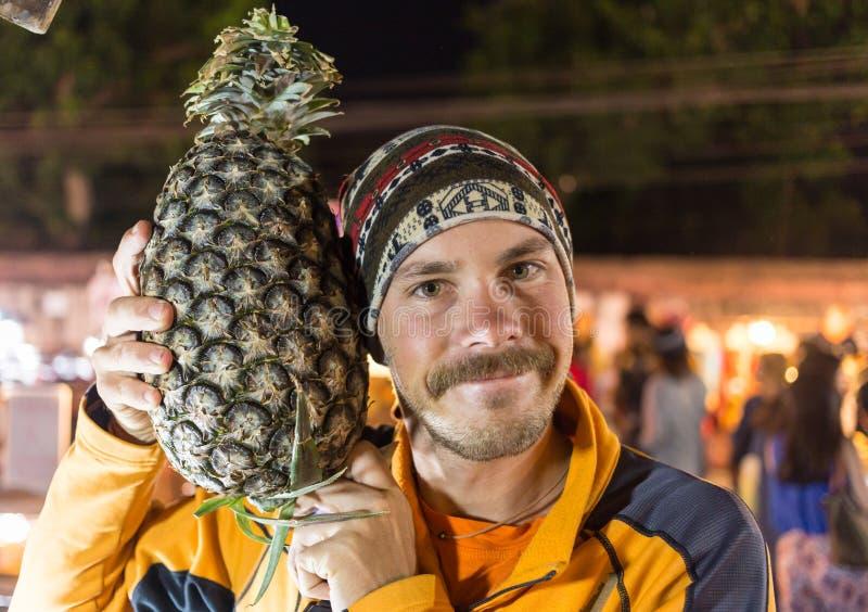 Portrait d'homme drôle avec le grand ananas photographie stock