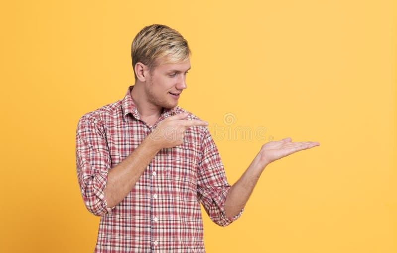 Portrait d'homme gai dirigeant des doigts au copyspace d'isolement au-dessus du fond jaune image stock