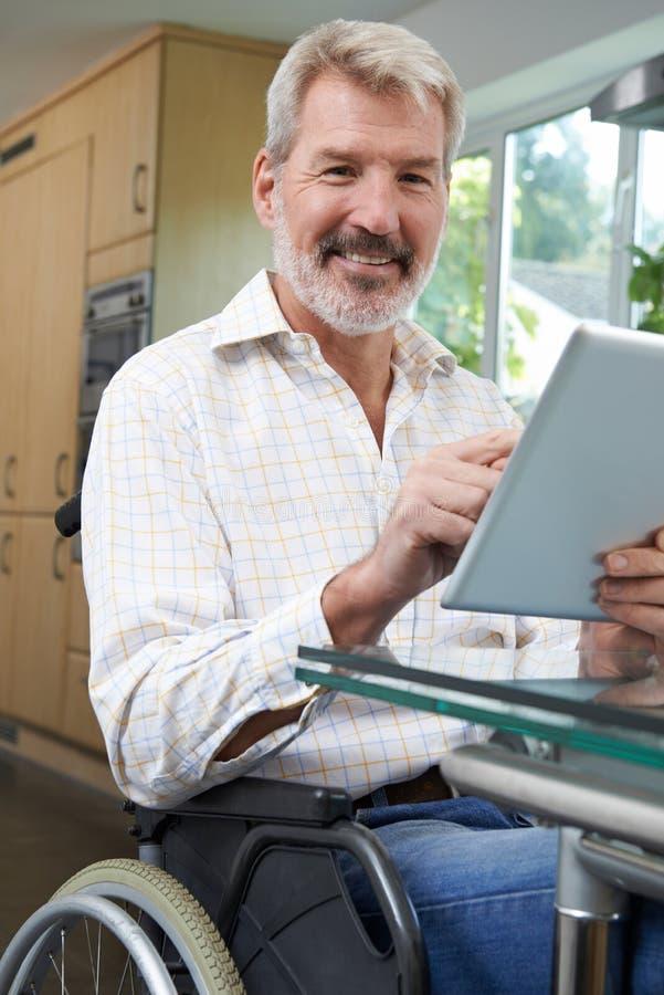 Portrait d'homme handicapé dans le fauteuil roulant utilisant la Tablette de Digital à H photo libre de droits