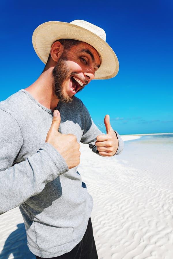 Portrait d'homme heureux dans le chapeau blanc sur la plage sablonneuse blanche photos stock