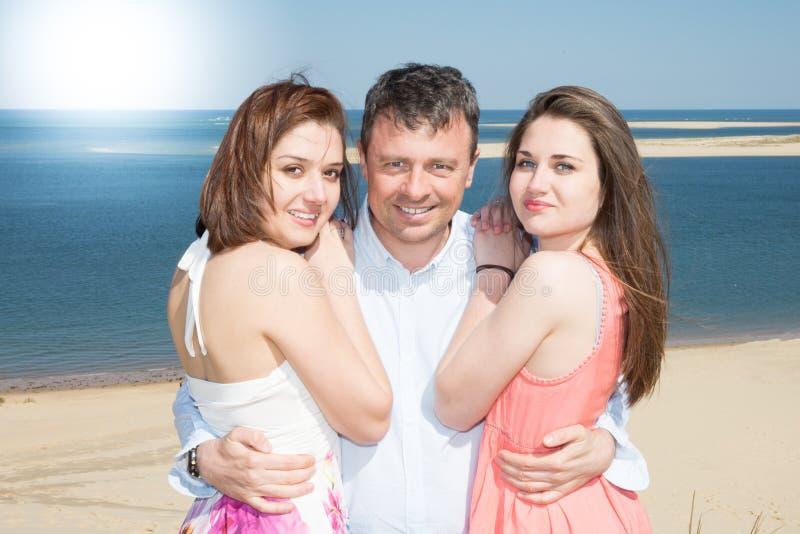 Portrait d'homme heureux entre deux filles se tenant sur le sable des vacances d'été image libre de droits