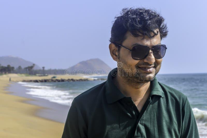 Portrait d'homme indien élégant dans le T-shirt et des lunettes de soleil formels dehors, milieux de mer photographie stock libre de droits