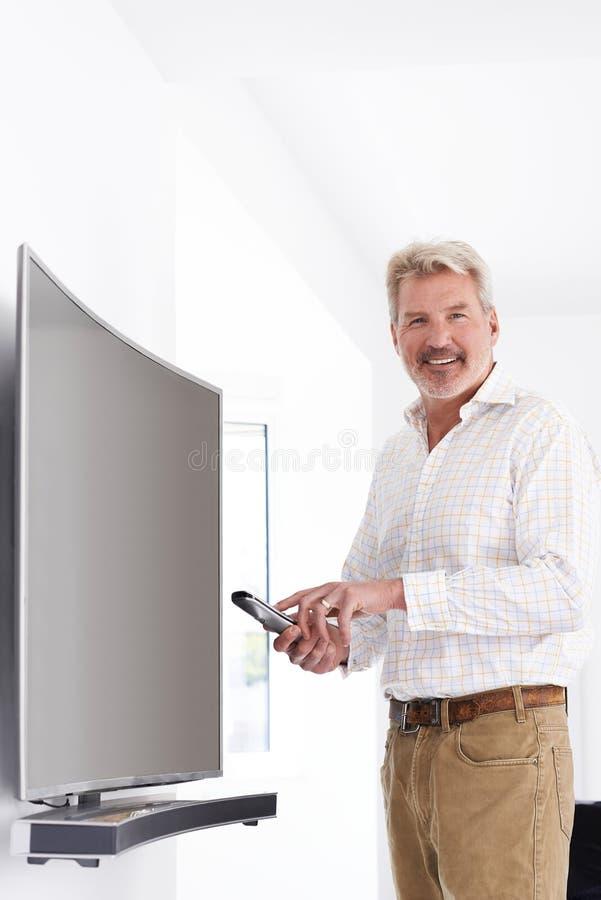 Portrait d'homme mûr avec la nouvelle télévision incurvée d'écran à la maison image libre de droits