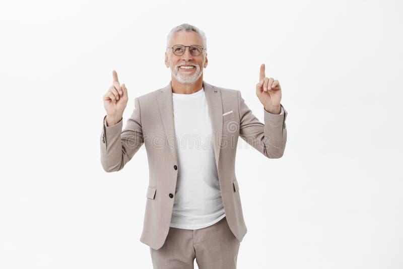 Portrait d'homme mûr impressionné et avec plaisir enthousiaste avec les cheveux et la barbe gris en verres et de costume regardan photo stock