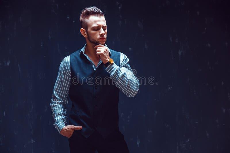 Portrait d'homme macho sexy au-dessus du fond foncé utilisant une montre-bracelet de chronographe photos stock