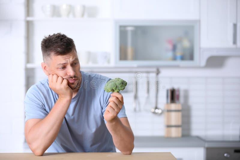 Portrait d'homme malheureux regardant le brocoli dedans photo stock