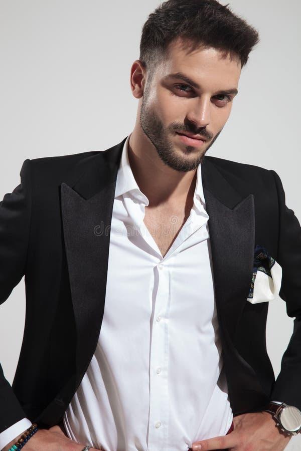 Portrait d'homme séduisant de mode dans le costume noir tenant des hanches image stock