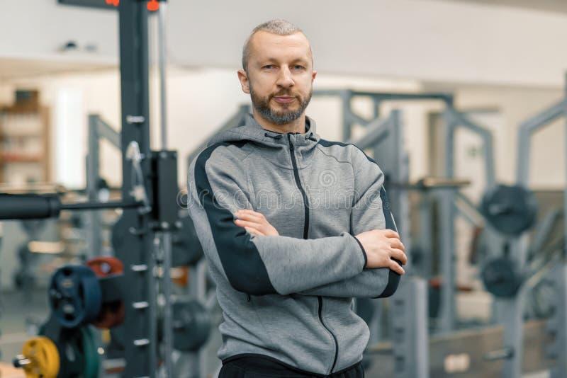Portrait d'homme sportif avec les mains pliées dans le gymnase, entraîneur barbu bel regardant la caméra images stock