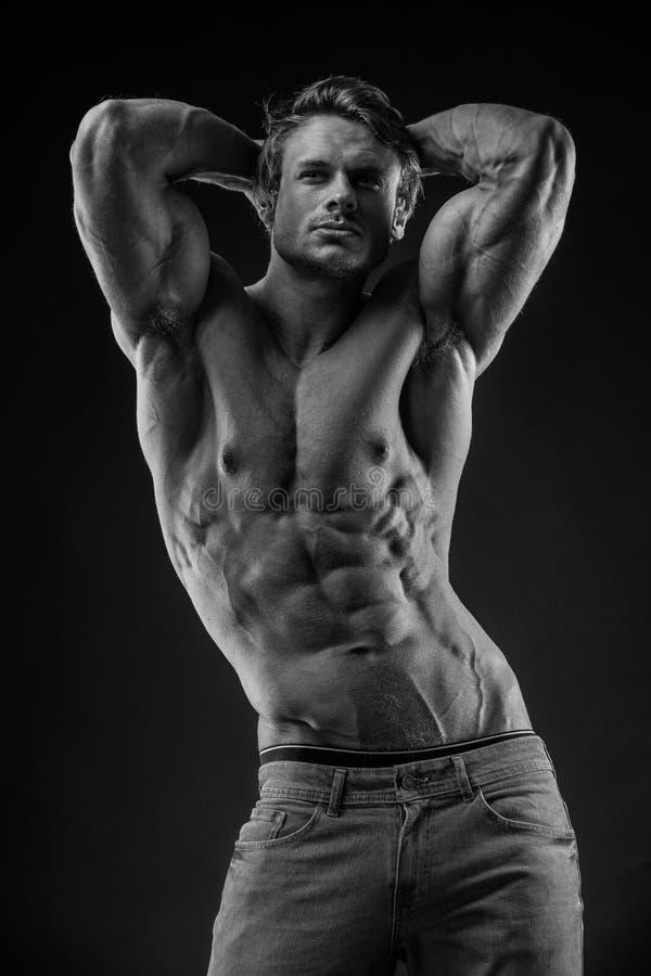 Portrait d'homme sportif fort de forme physique au-dessus de fond noir image stock