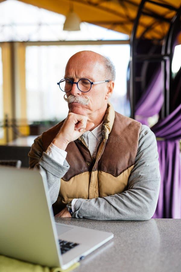 Portrait d'homme supérieur animé tout en travaillant avec l'ordinateur portable moderne à la table du café extérieur le jour lumi image stock