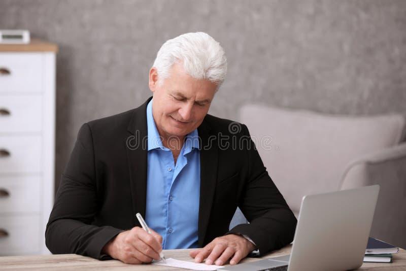 Portrait d'homme supérieur complétant le billet de loterie images stock