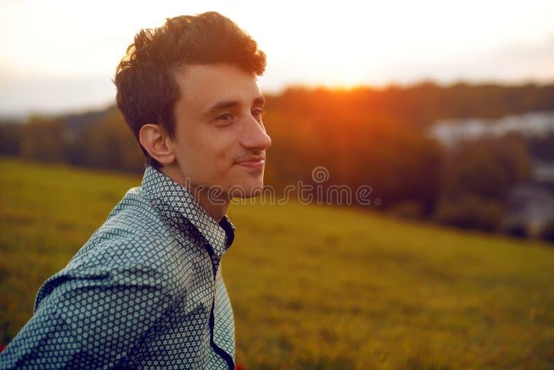 Portrait d'homme sur le coucher du soleil Équipez se reposer au parc un jour d'été, garçon de sourire Étudiant après collage, hom images libres de droits