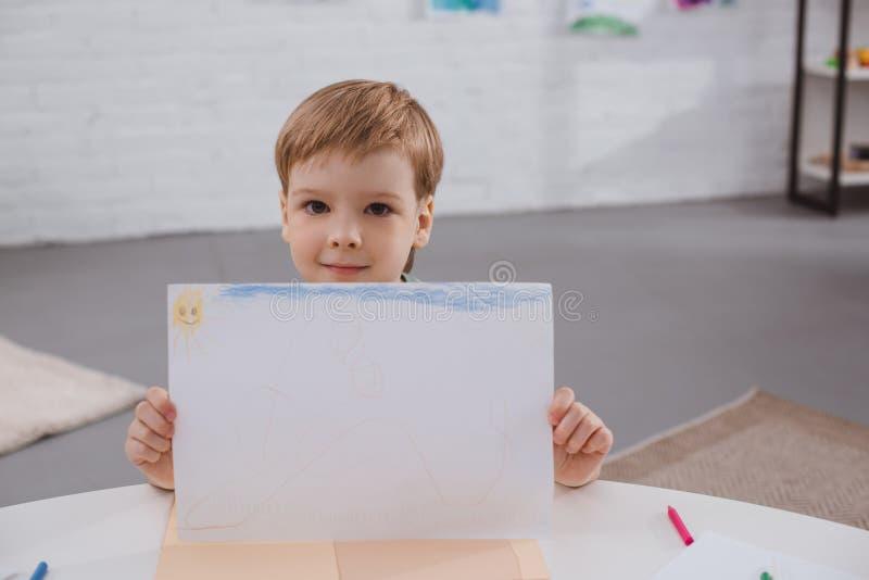 portrait d'image mignonne d'apparence de garçon dans des mains à la table photo libre de droits