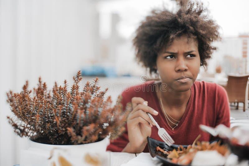 portrait d'Inclinaison-décalage de la fille brésilienne songeuse mangeant dans la rue c photographie stock libre de droits