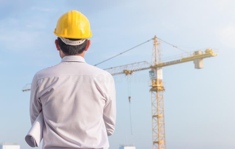 Portrait d'ingénieur porter la sécurité jaune de casque et tenir le modèle au chantier de construction avec le fond de grue photo stock