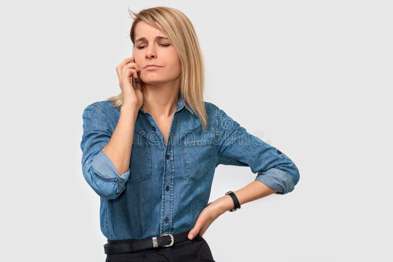 Portrait d'intérieur de conseillère caucasienne sérieuse de femme dans la chemise de denim, ayant sur la conversation de téléphon photos stock