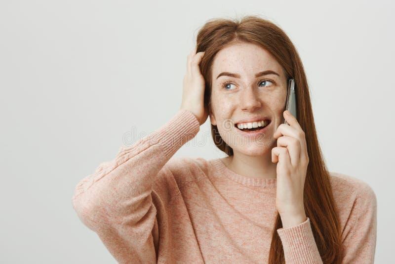 Portrait d'intérieur de la fille européenne féminine de gingembre avec des taches de rousseur parlant au téléphone tout en rayant photo stock