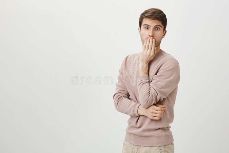 Portrait d'intérieur d'homme adulte mignon et bel avec le poil se tenant dans la pose étonnée ou étonnée avec la main près photographie stock libre de droits
