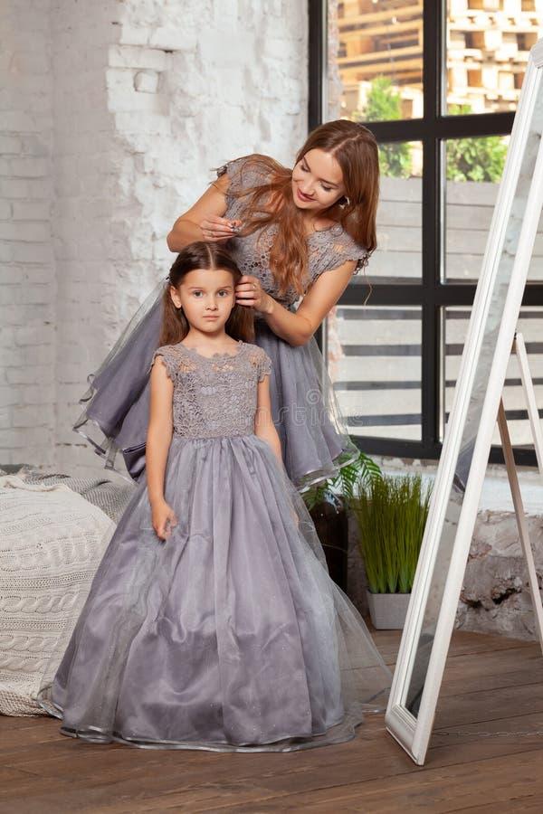 Portrait d'intérieur d'une belle mère avec elle petite fille avec du charme posant contre l'intérieur de chambre à coucher image stock
