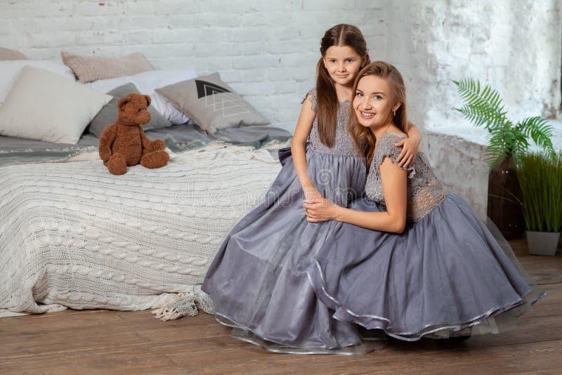 Portrait d'intérieur d'une belle mère avec elle petite fille avec du charme posant contre l'intérieur de chambre à coucher photographie stock libre de droits
