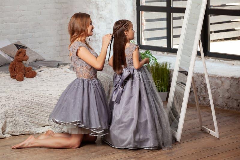 Portrait d'intérieur d'une belle mère avec elle petite fille avec du charme posant contre l'intérieur de chambre à coucher photo libre de droits