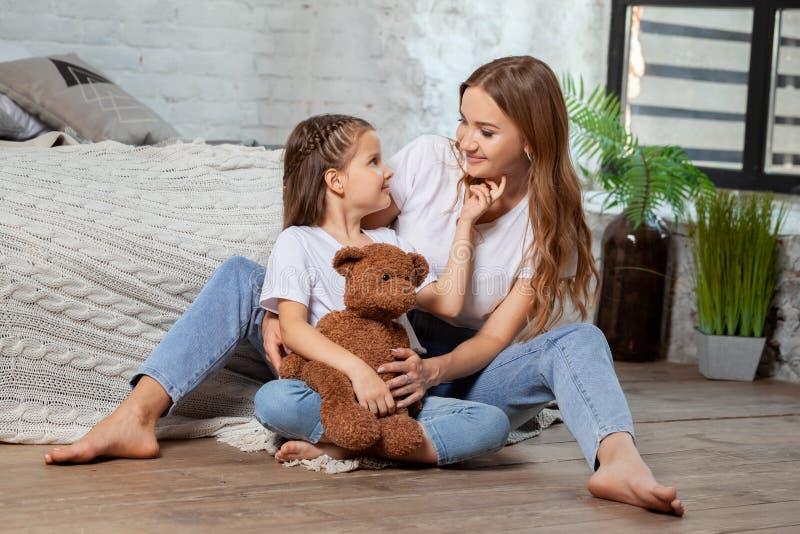 Portrait d'intérieur d'une belle mère avec elle petite fille avec du charme posant contre l'intérieur de chambre à coucher photos stock