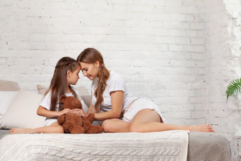 Portrait d'intérieur d'une belle mère avec elle petite fille avec du charme posant contre l'intérieur de chambre à coucher photographie stock
