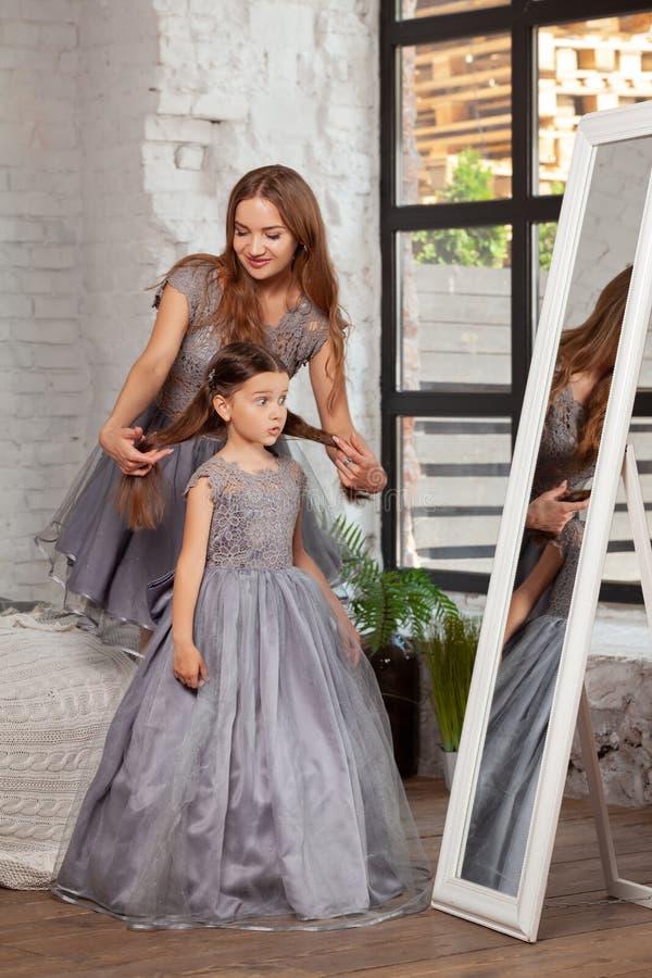 Portrait d'intérieur d'une belle mère avec elle petite fille avec du charme posant contre l'intérieur de chambre à coucher image libre de droits