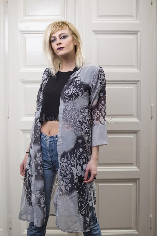 Portrait d'int?rieur de mode attrayante de la belle fille blonde posant devant la porte blanche photographie stock libre de droits