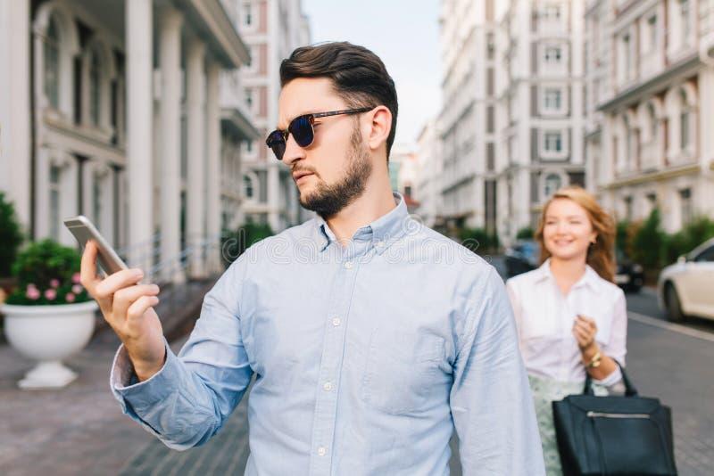 Portrait d'intestin un peu triste dans des lunettes de soleil regardant au téléphone sur la rue Jolie fille blonde l'attrapant pa photos stock