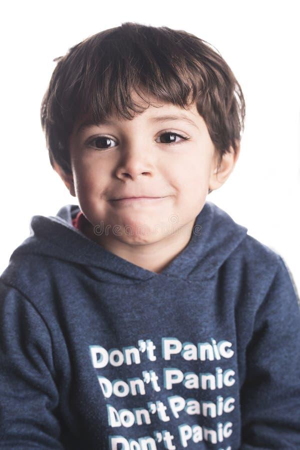 Portrait d'isolement de petit garçon regardant la caméra et le sourire photographie stock